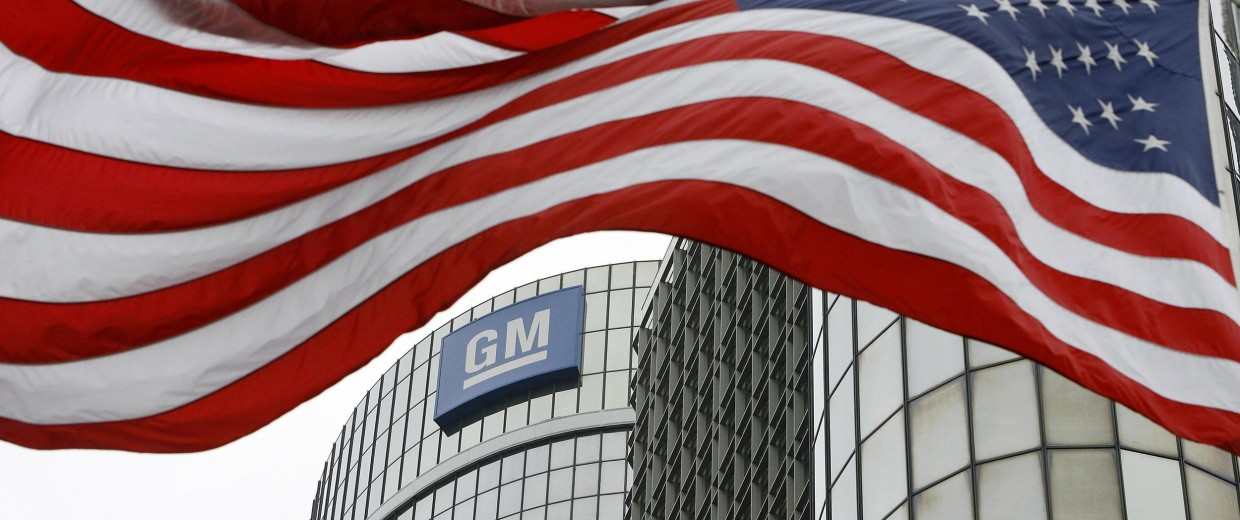 Image: An American flag flies in front of the General Motors, Global Headquarters in Detroit, Michigan