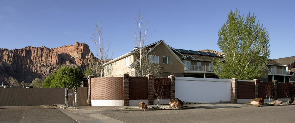 """Image: Tall walls, fences and """"no access"""" signs surrounds the homes of Warren Jeffs on April 20, 2006 in Hildale, Utah."""