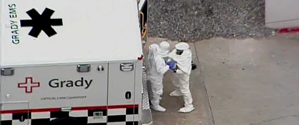 Image: Two men in protective suits leave an ambulance at Emory University Hospital