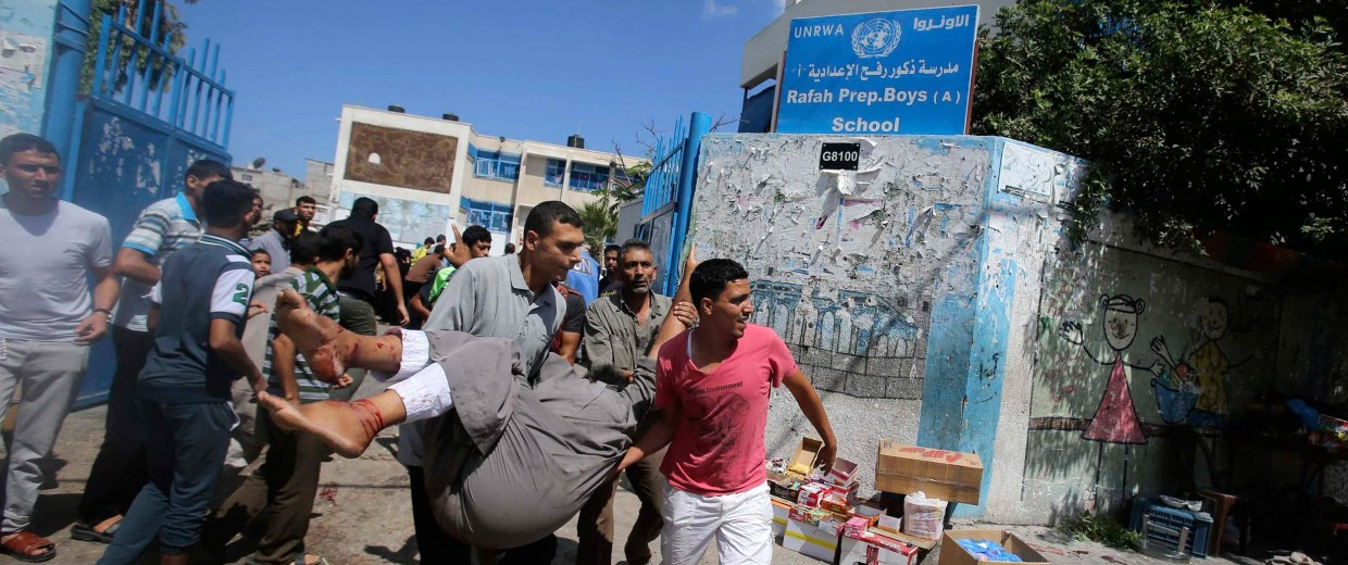 Image: Palestinians carry a wounded man following what witnesses said was an Israeli air strike at a U.N.-run school in Rafah