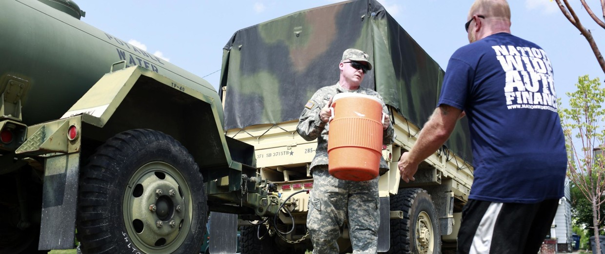 Image: Ohio Army National Guard Spc. Ruebin Miller, left, carries a container of fresh drinking water to Toledo resident Mark Piotrowski