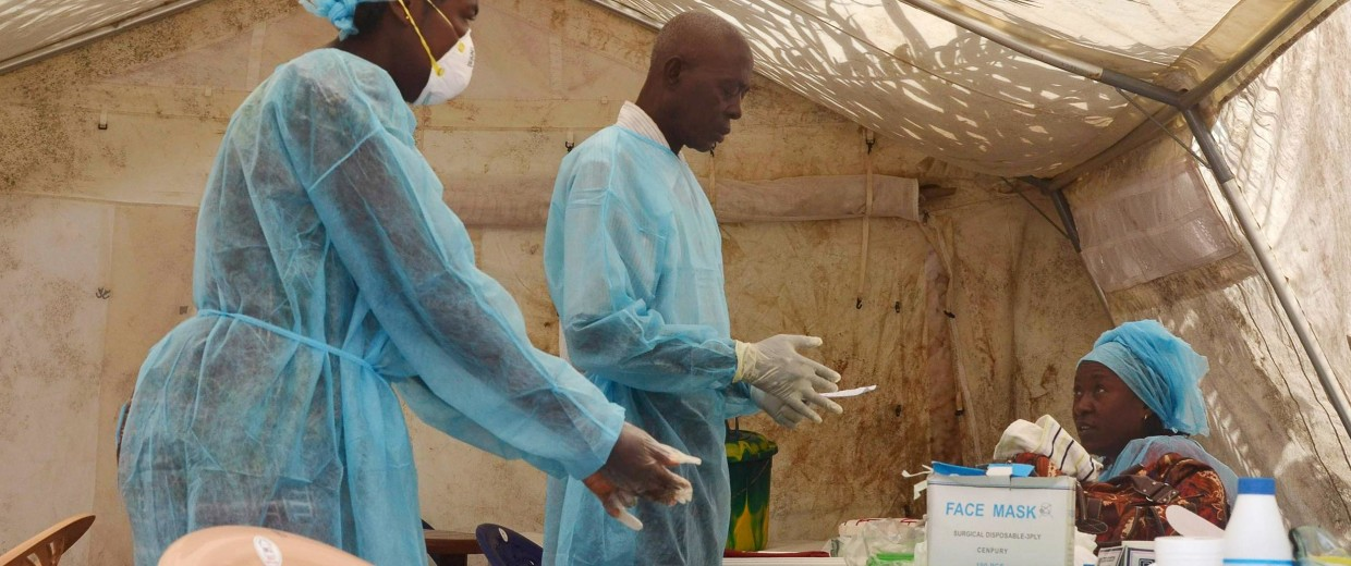 Image: Health workers take blood samples for Ebola virus testing at a screening tent in the local government hospital in Kenema