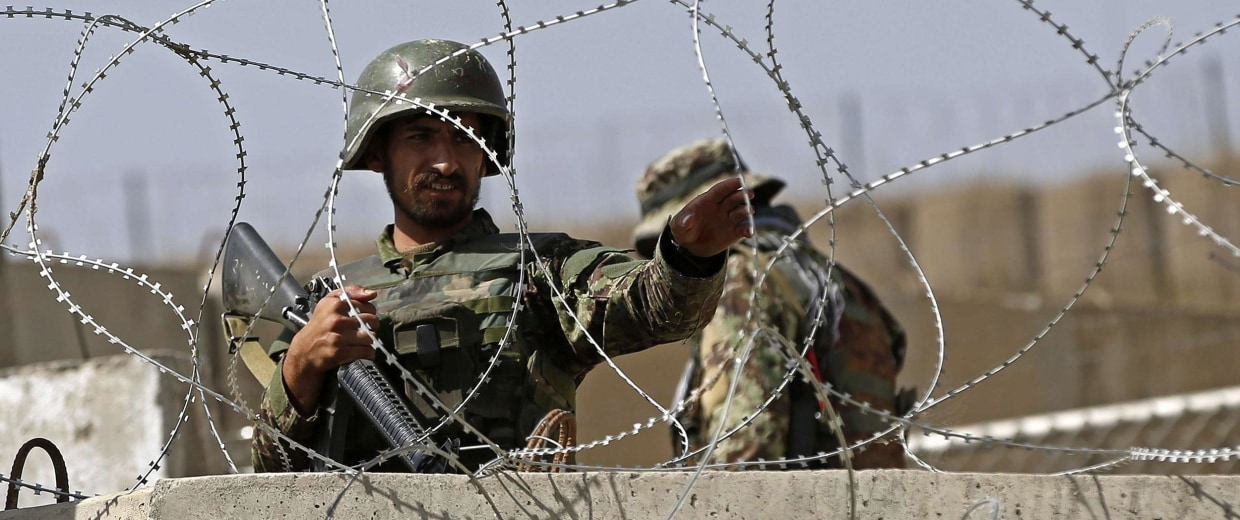 Image: Afghan National Army soldier keeps watch at gate of a British-run military training academy Camp Qargha, in Kabul
