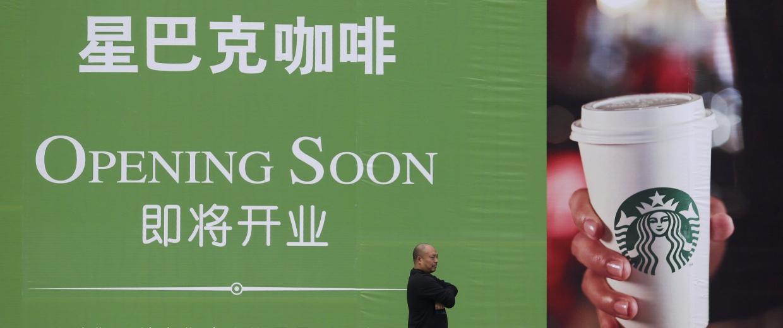 Image: Man walking past an advertisement board of Starbucks in Wuhan