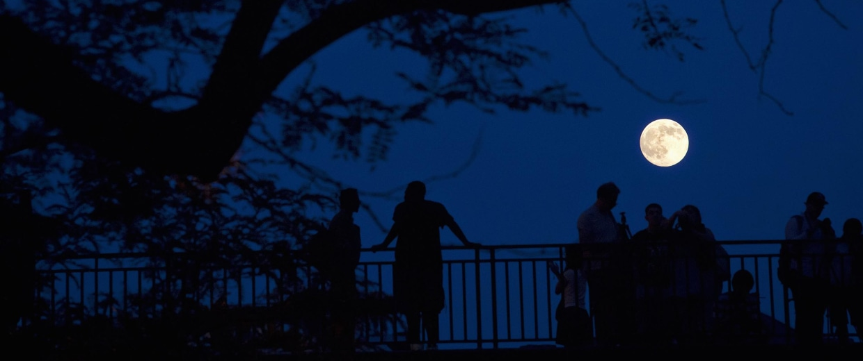 Image: People stand and look at the moon one day ahead of the Supermoon phenomenon from a bridge over 42nd St. in the Manhattan borough of New York