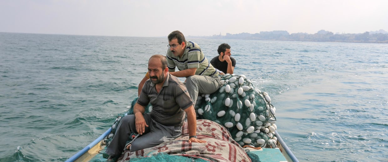 Ibrahim Bakir, a fisherman from Gaza on his boat with other family members by the shore of Gaza city on Friday August 15, 2014.