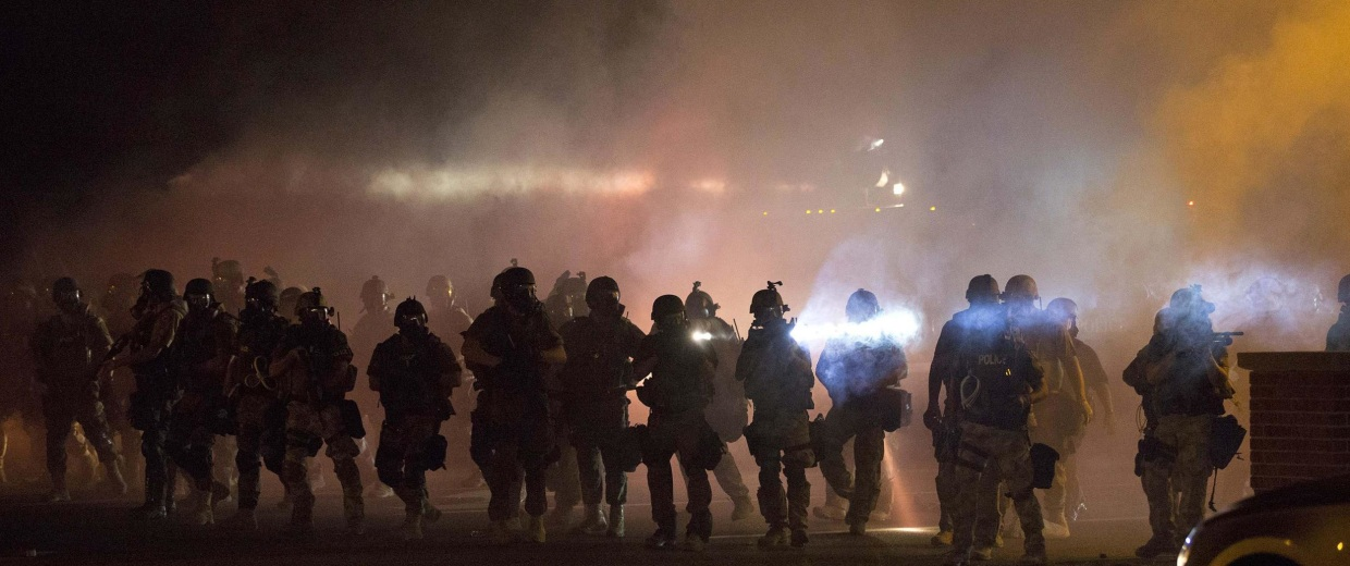 Image: Riot police clear demonstrators from a street in Ferguson