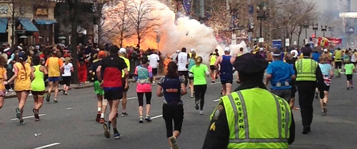 Image: File photo of runners running towards the finish line as an explosion erupts at the finish line of the Boston Marathon