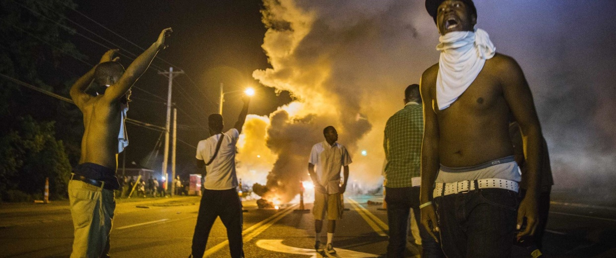 Image: Demonstrators stand in the middle of West Florissant as they react to tear gas fired by police during ongoing protests in reaction to the shooting of Michael Brown, in Ferguson