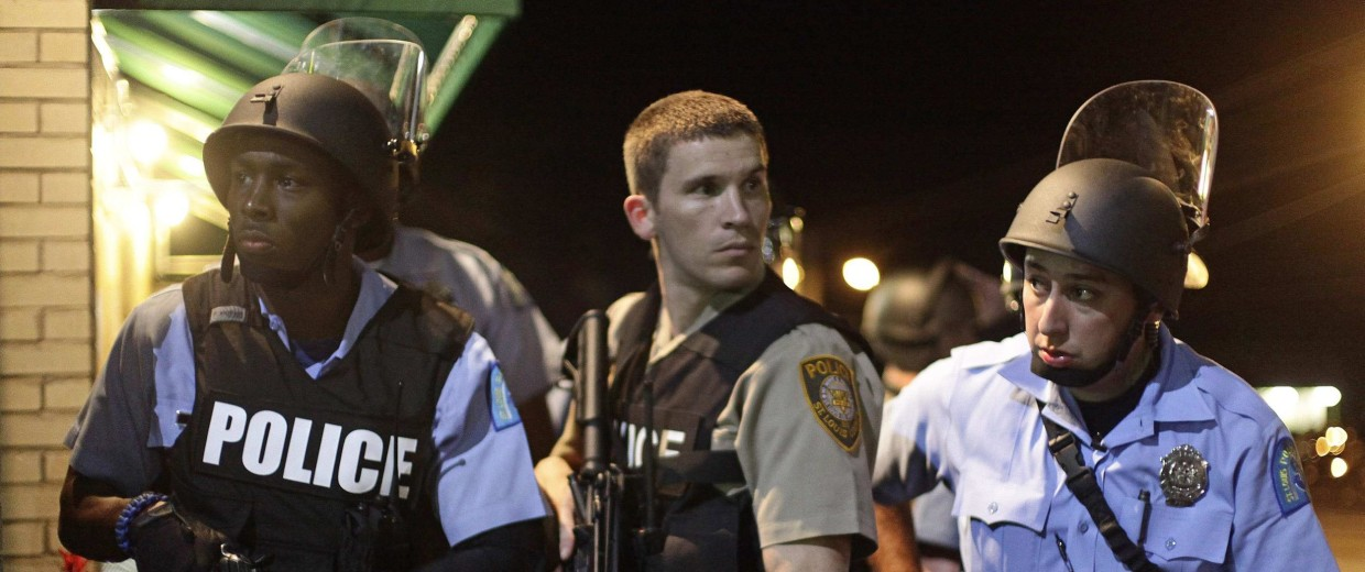 Image: Police officers hold their weapons as they watch demonstrators protest against the shooting of Michael Brown in Ferguson