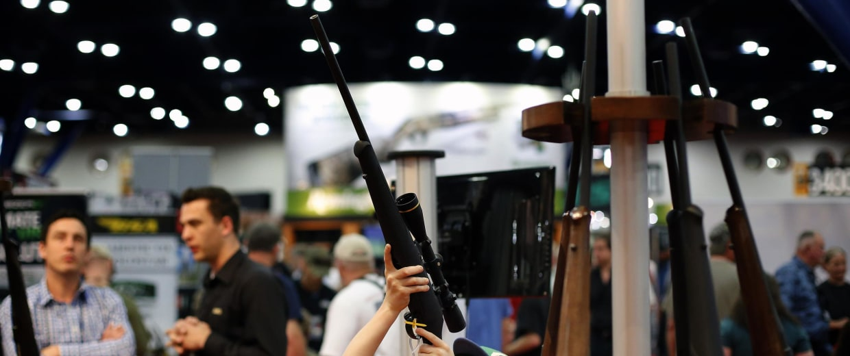 Image: 11-year-old Ryan Weaver inspects a rifle, during an NRA convention in Houston.