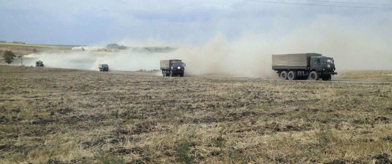 Image: Military trucks travel through the steppe near the village of Krasnodarovka