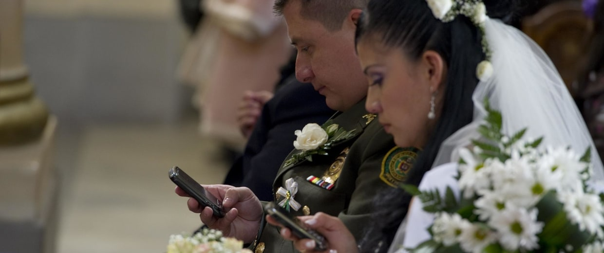 A bride and groom use their mobile phone