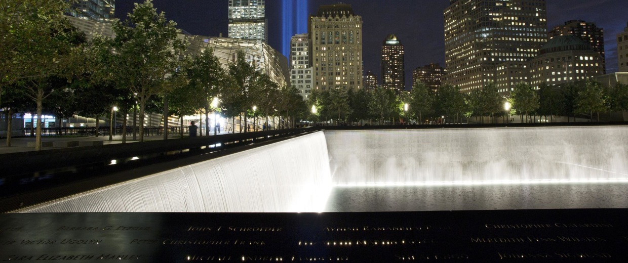 Image: The Tribute in Light rises behind buildings adjacent to the 1 World Trade Center and a reflecting pool at the National September 11 Memorial