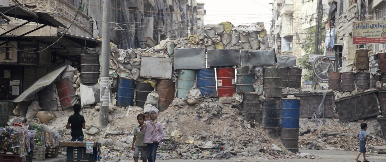 Image: Children walk in front of barrels and sandbags stacked up in a makeshift cover for protection against sniper fire in the East Al-Ansari neighborhood of Aleppo