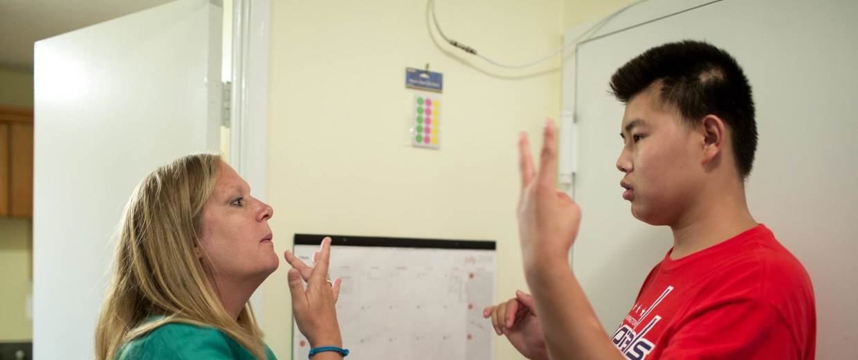 Image:Christine Ogden converses using sign language with her adopted son Daniel