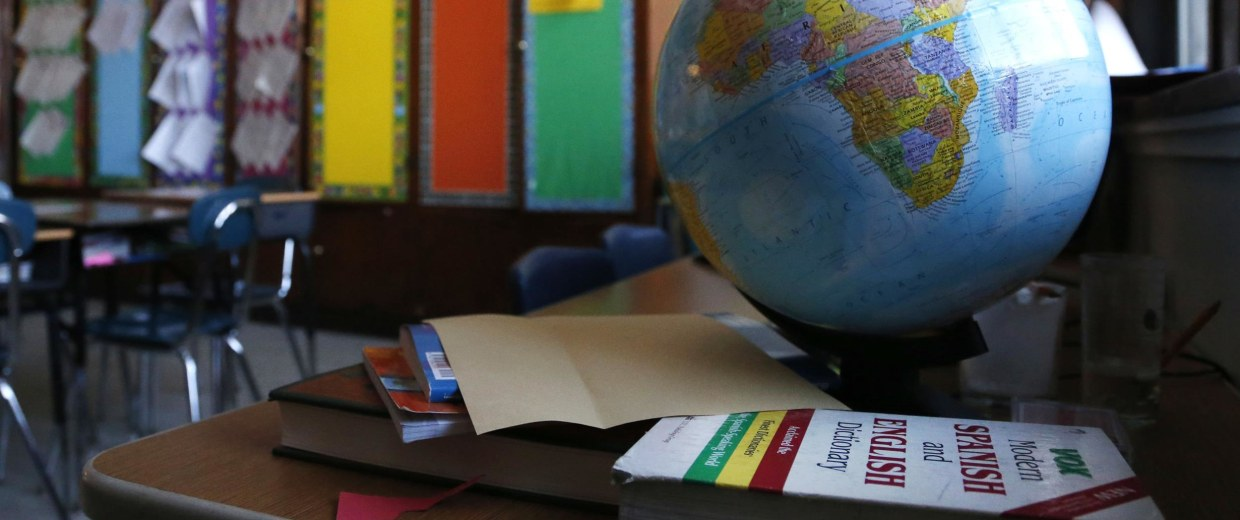 Image: A globe sits on a desk in a classroom.