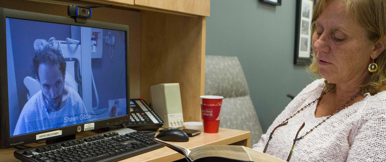 Image: Debbie Sacra, wife of Dr. Rick Sacra, reading Bible verses to him during a video conference at the Nebraska Medical Center in Omaha, Nebraska