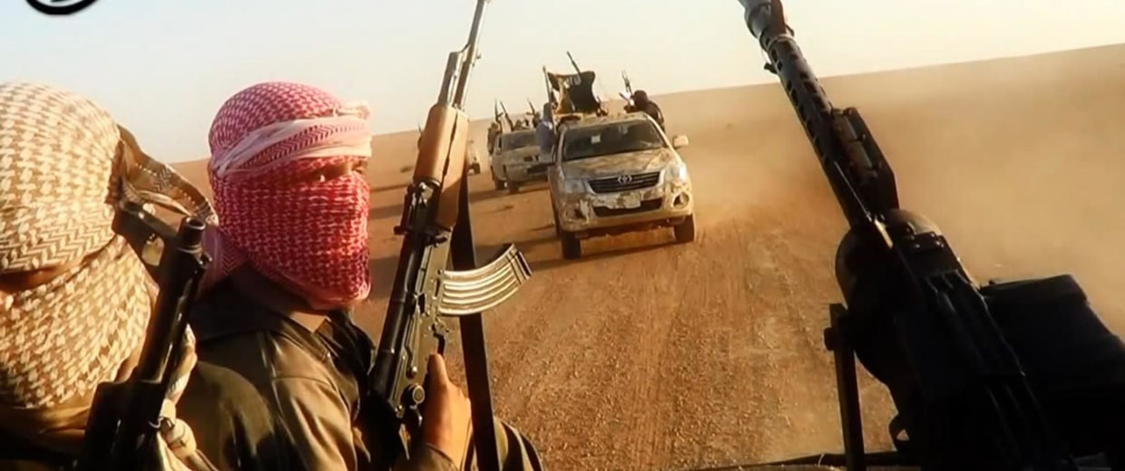 Image: ISIL militants driving in vehicles near the central Iraqi city of Tikrit