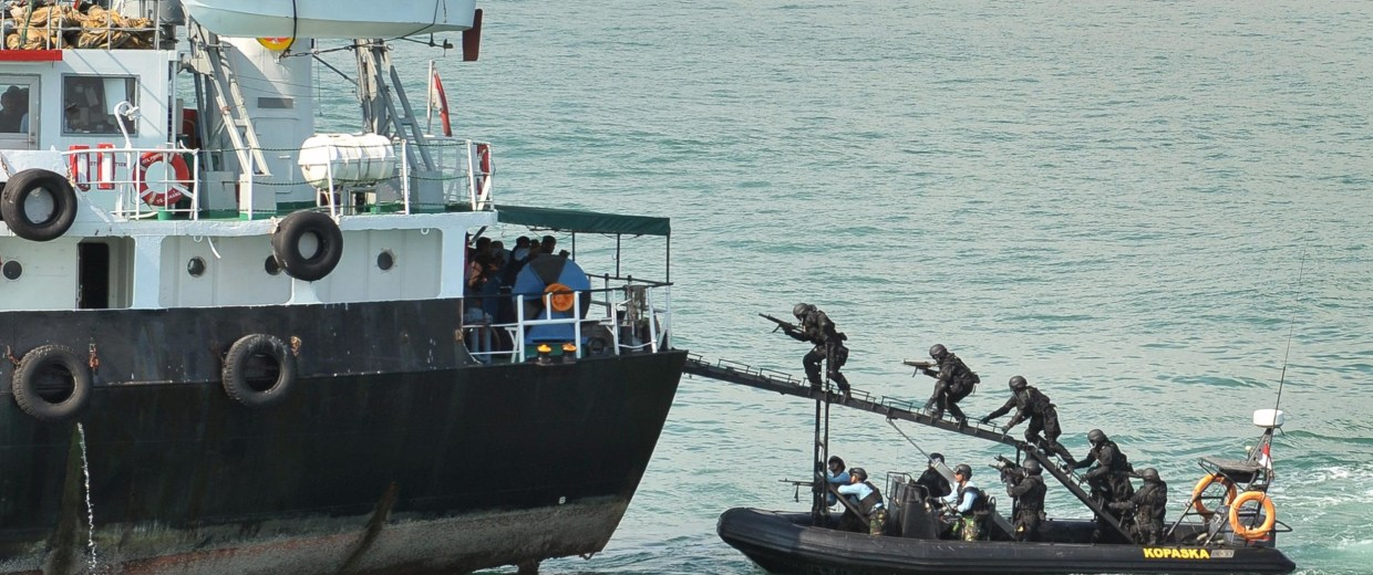 "Indonesian Navy Kopaska troops storm the ""hijacked"" vessel, MT Promise (L), off the Batam island."