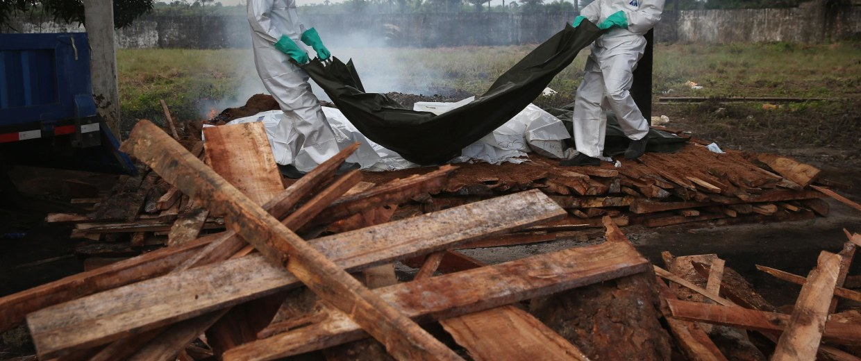 Image: A burial team from the Liberian Ministry of Health unloads the bodies of Ebola victims onto a funeral pyre