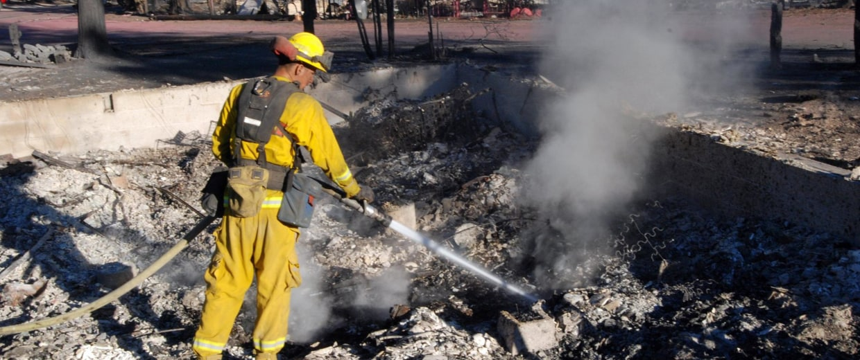 Image: A firefighter hoses down smoking rubble