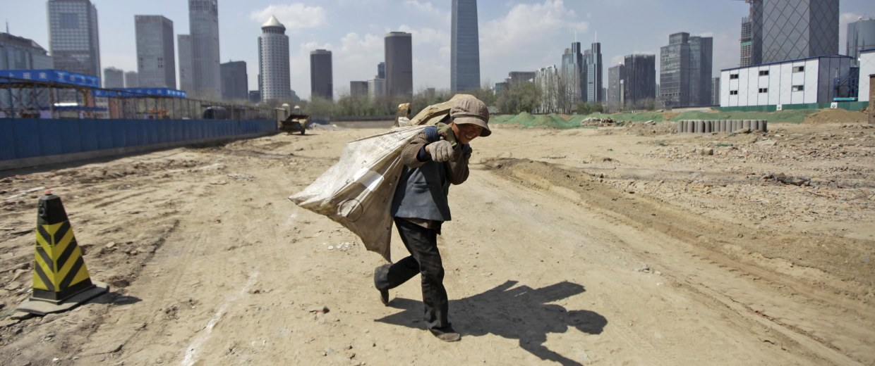 Image: A waste collector carries a sack of recycled material as she leaves a construction site in Beijing's central business district