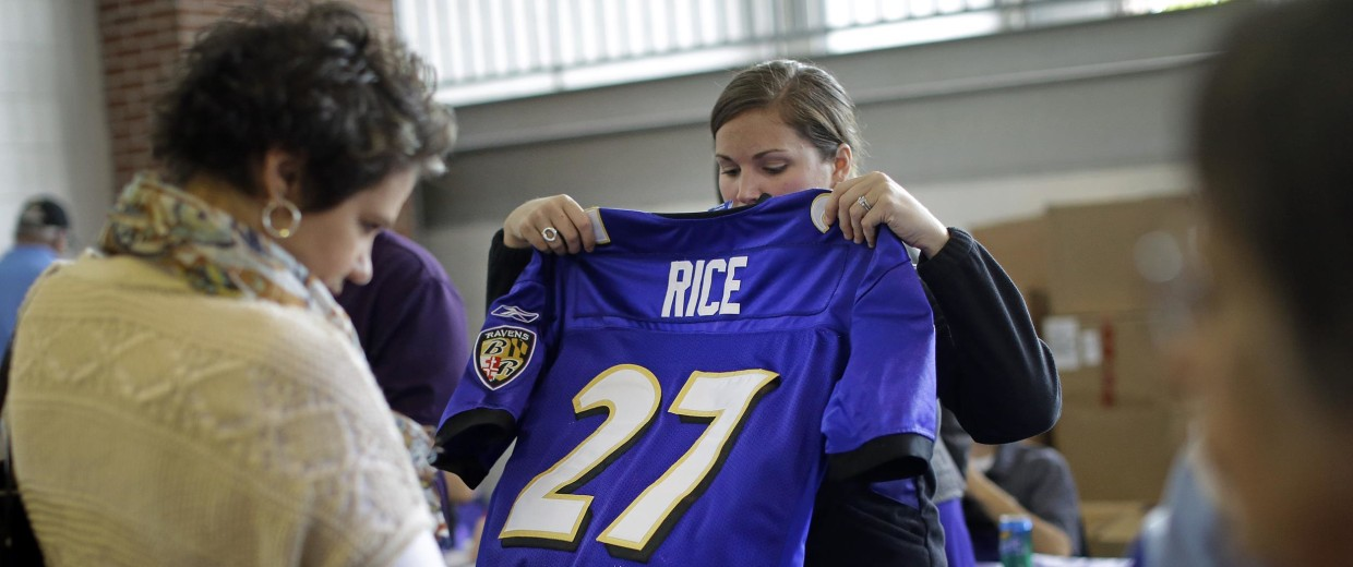Image: A worker folds up a former Baltimore Ravens running back Ray Rice jersey that a fan traded in