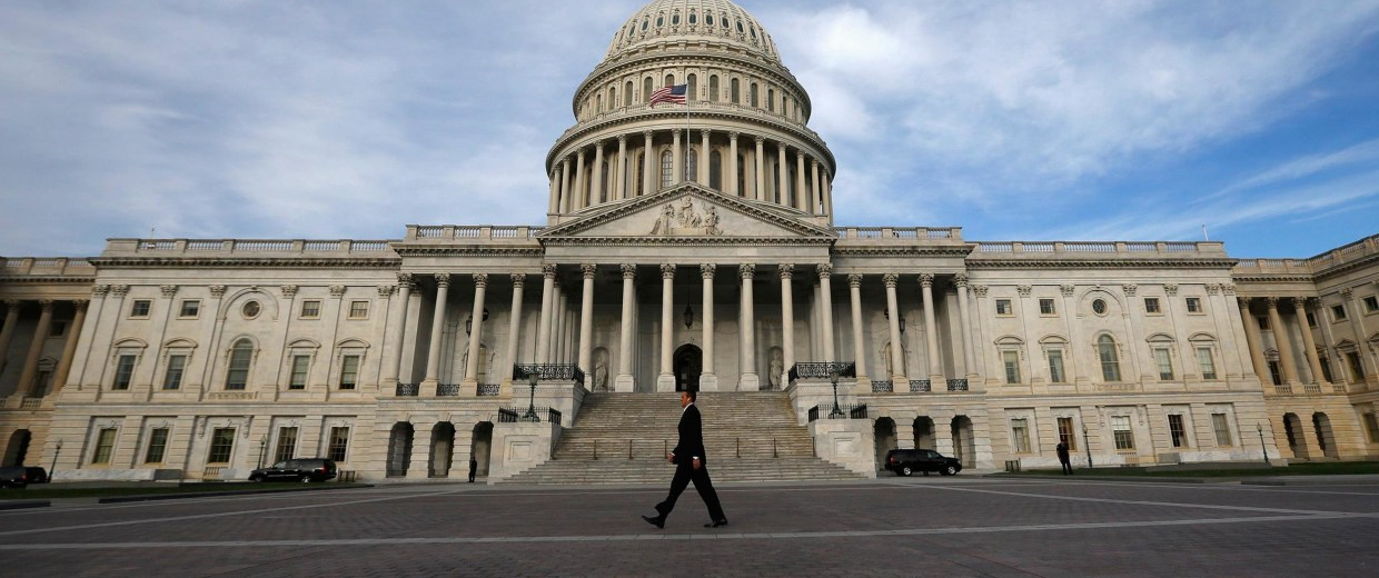 Image: A lone worker passes by the U.S. Capitol building in Washington