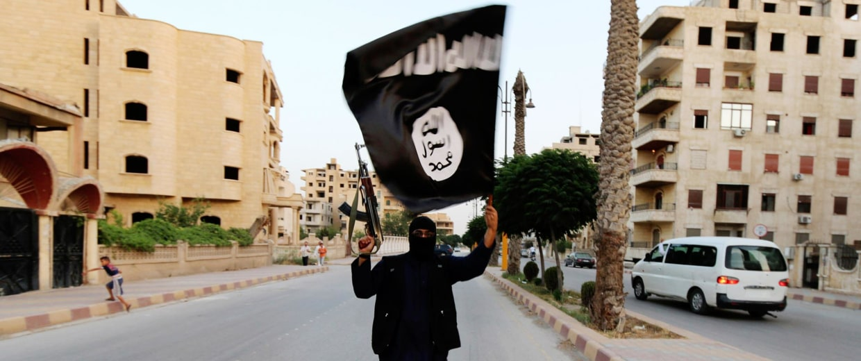 Image: A member loyal to the ISIL waves an ISIL flag in Raqqa