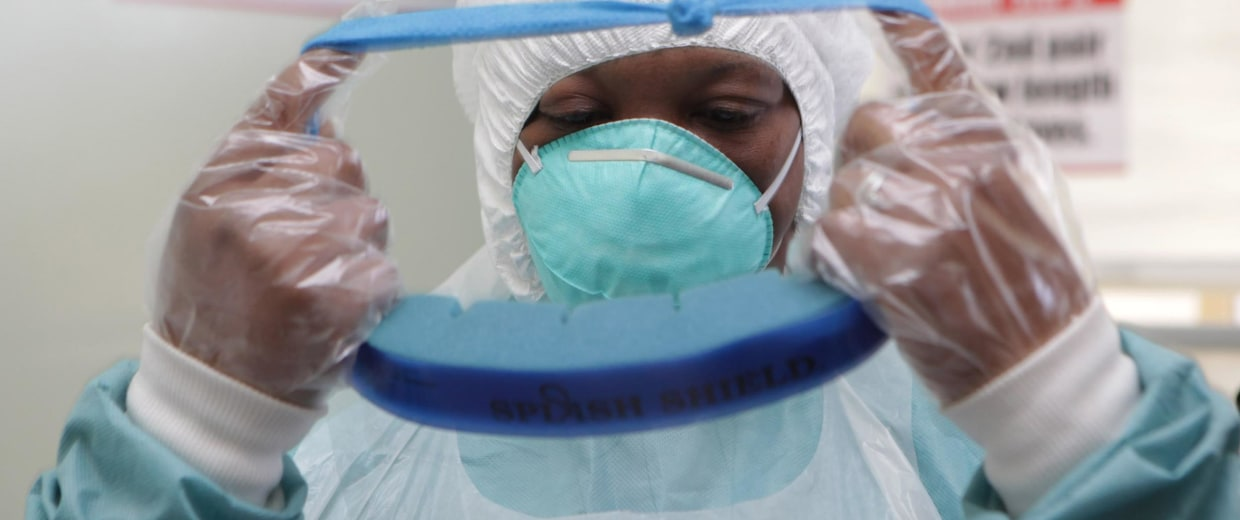 Image: A woman wears protective clothing during a tour of one of the Ebola Centers in Harare, Zimbabwe, on Sept. 23.