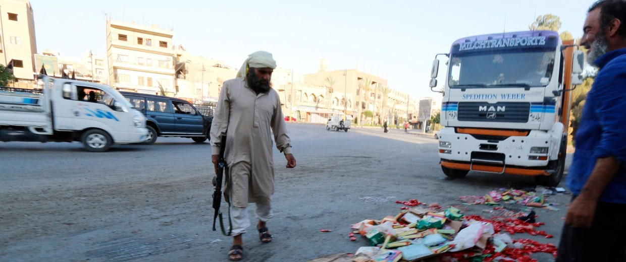 Image: An Islamic State fighter keeps guard as people, who according to them are employees of the Islamic State hired to monitor and check the quality of goods in markets, throw confiscated products in central Raqqa