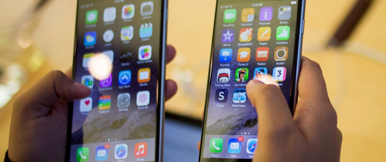 Image: A customer holds an iPhone 6 and iPhone 6 Plus