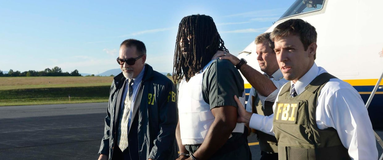 Image: FBI agents escort Jesse Leroy Matthew, Jr., center, from a plane during extradition to Charlottesville, Va.