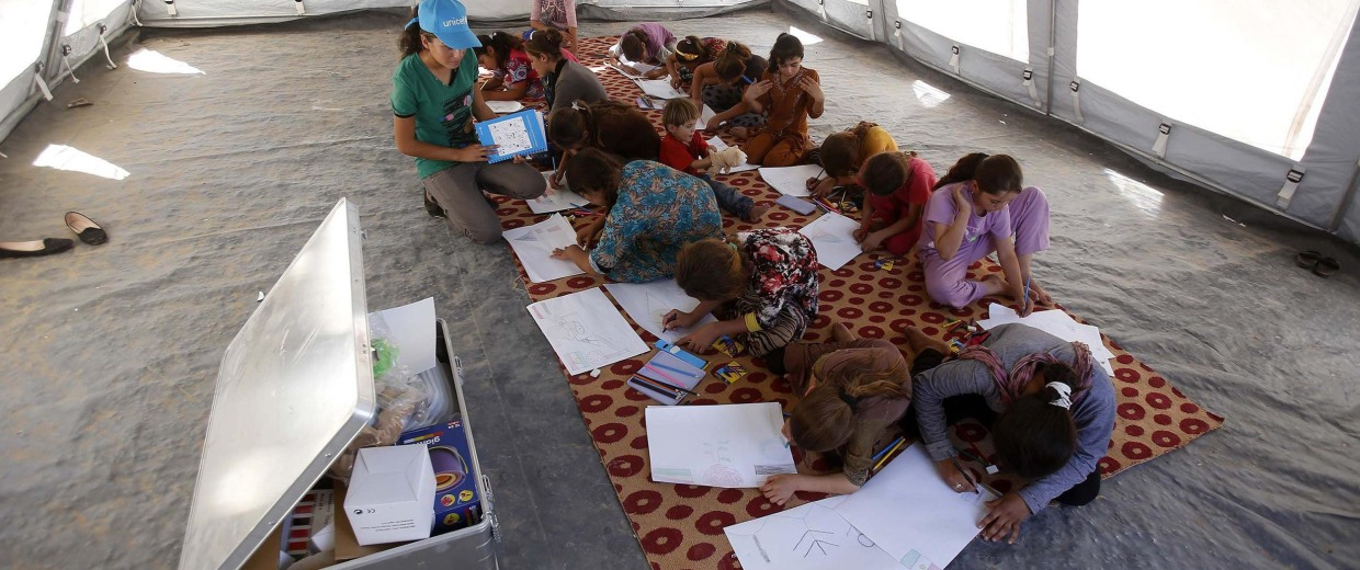 Image: Young displaced Iraqis, who have fled the violence in the country, attend a drawing class on September 13, 2014 at a camp for displaced people in Khanke