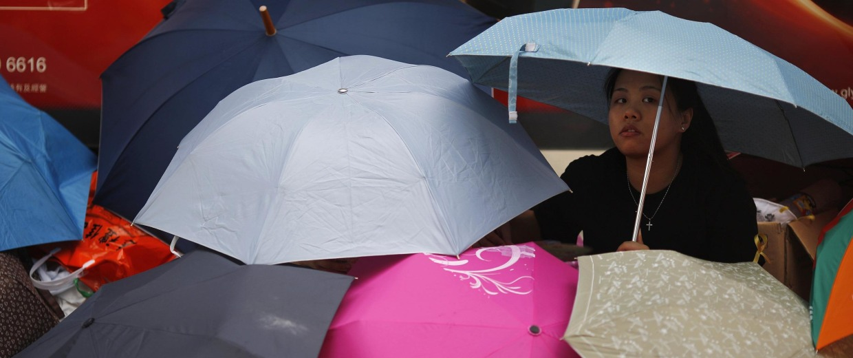 Image: A protester sits under umbrellas as she blocks the main street to the financial Central district outside the government headquarters in Hong Kong
