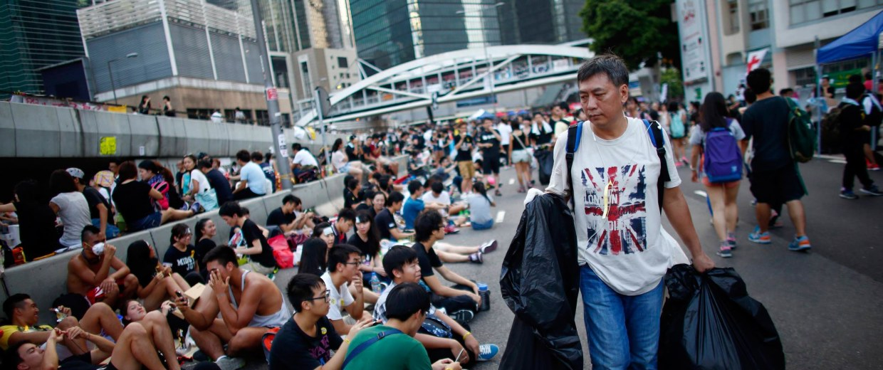 Image: A man picks up garbage along an area blocked by protesters outside of the government headquarters building in Hong Kong