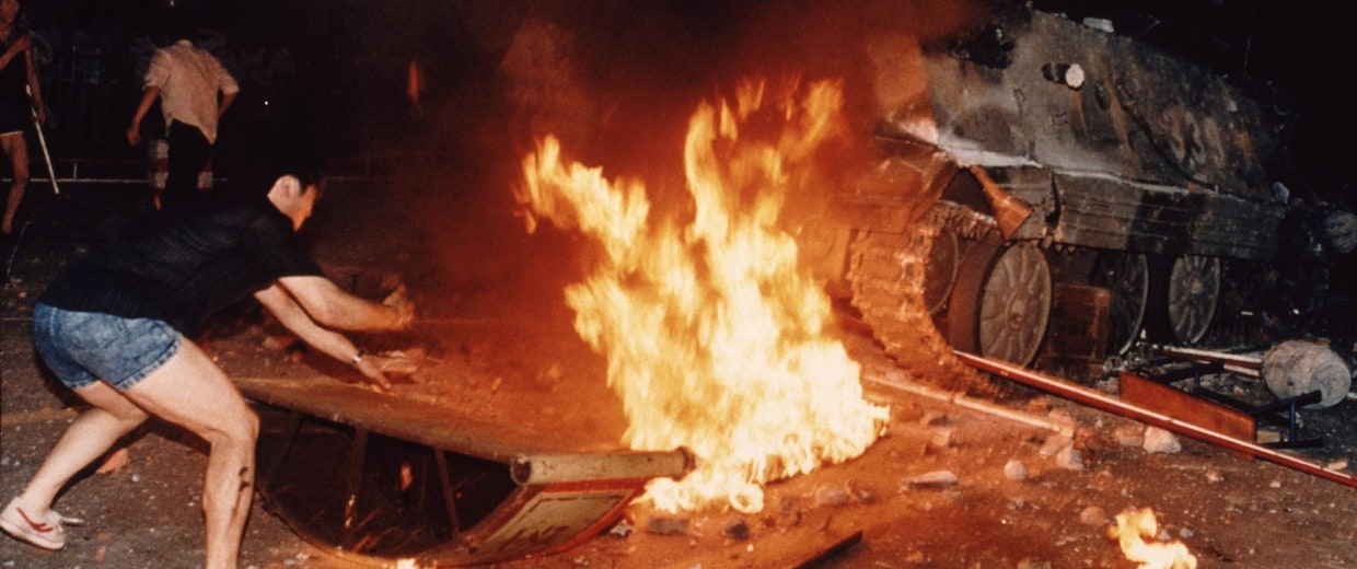 A student protester puts barricades in the path of an already burning armored personnel carrier