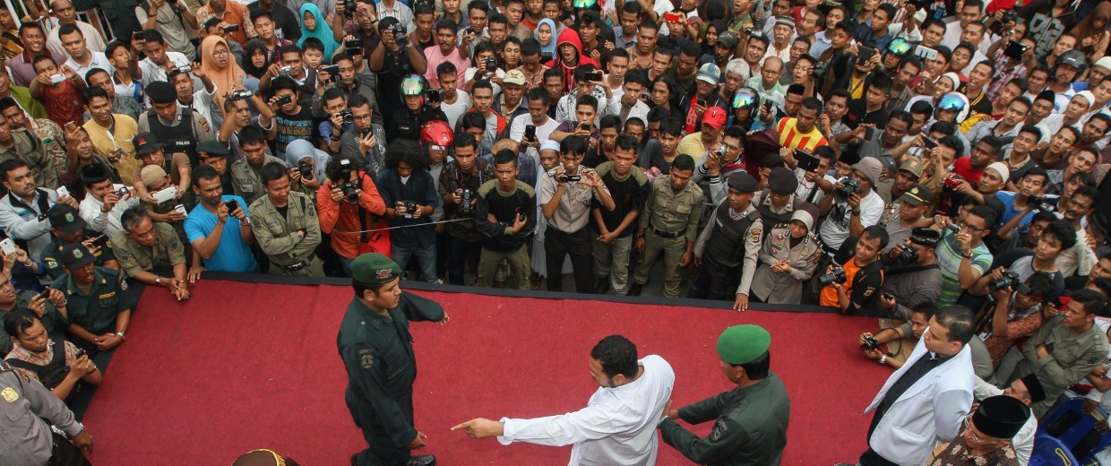 Image: An Acehnese man (center, in white) convicted of gambling gestures to a hooded officer during a public caning