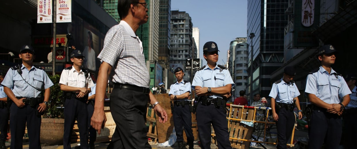 Image: Police guard a blockade set up by pro-democracy protesters in Hong Kong's Mongkok district