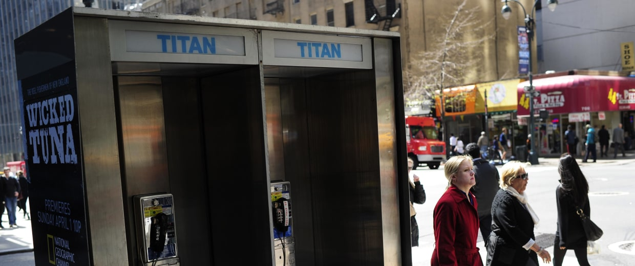 Image: People walk by empty public pay phone bo