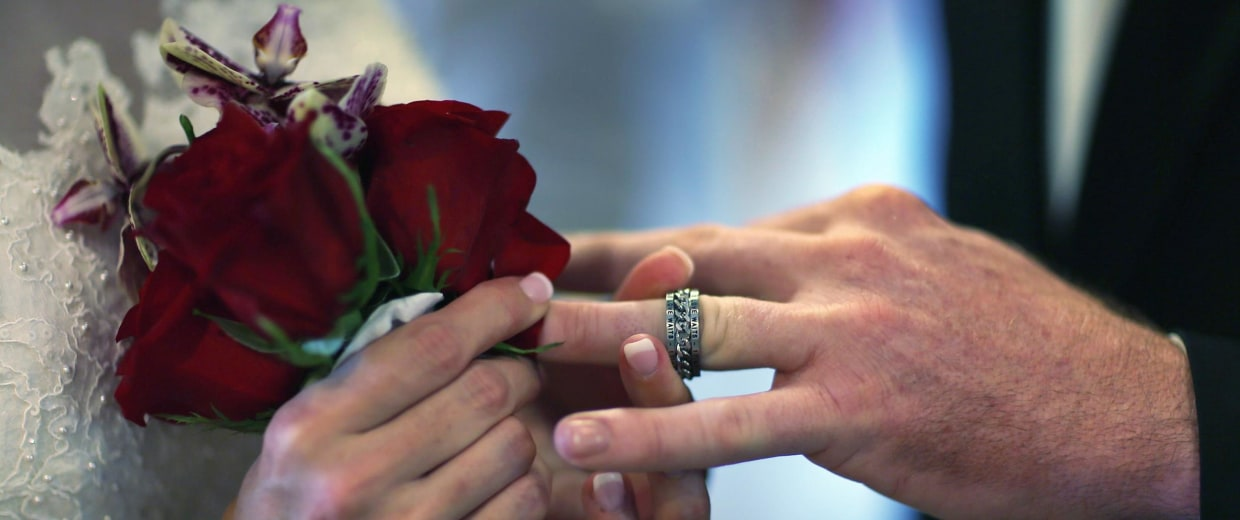 A bride slips a ring on the finger of her new husband