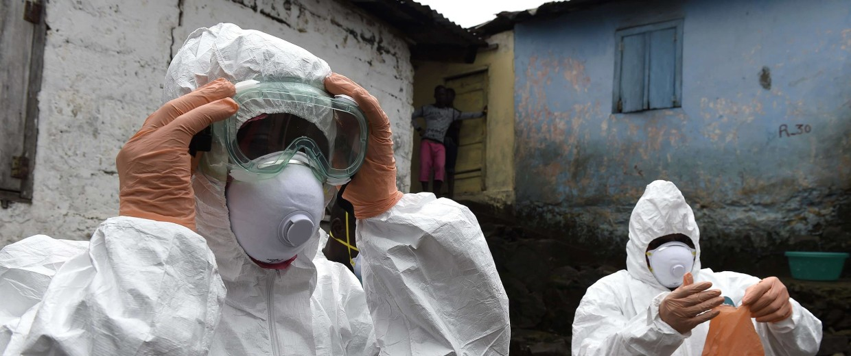 Image: Medical staff members of the Croix Rouge NGO put on protective suits before collecting the corpse of a victim of Ebola, in Monrovia