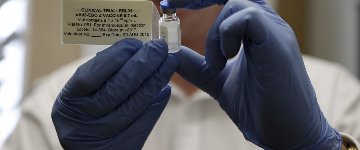 Image: Professor Adrian Hill, director of the Jenner Institute and chief investigator of the trials with the Ebola vaccine Chimp Adenovirus type 3 (ChAd3), holds a vial of the vaccine before injecting it into British volunteer Ruth Atkins