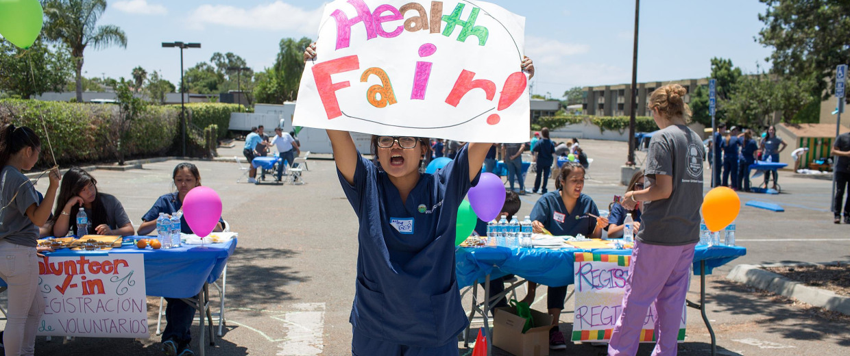 Image: Medical Pathways undergraduate Nina Forosan waves a sign at passing motorists encouraging them to stop at the free health fair