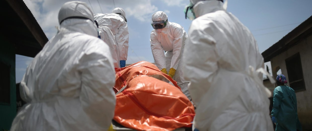 Image: An Ebola burial team loads the body of a woman, 54, onto a truck for cremation in Liberia