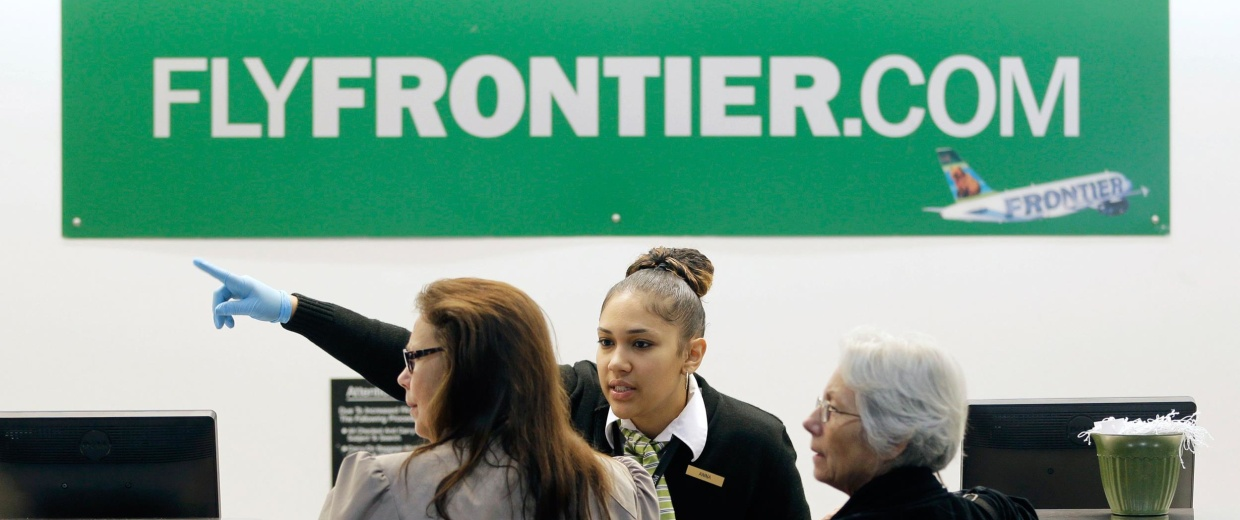 Image: A Frontier Airlines employee wears gloves as she directs passengers where to go at Cleveland Hopkins International Airport