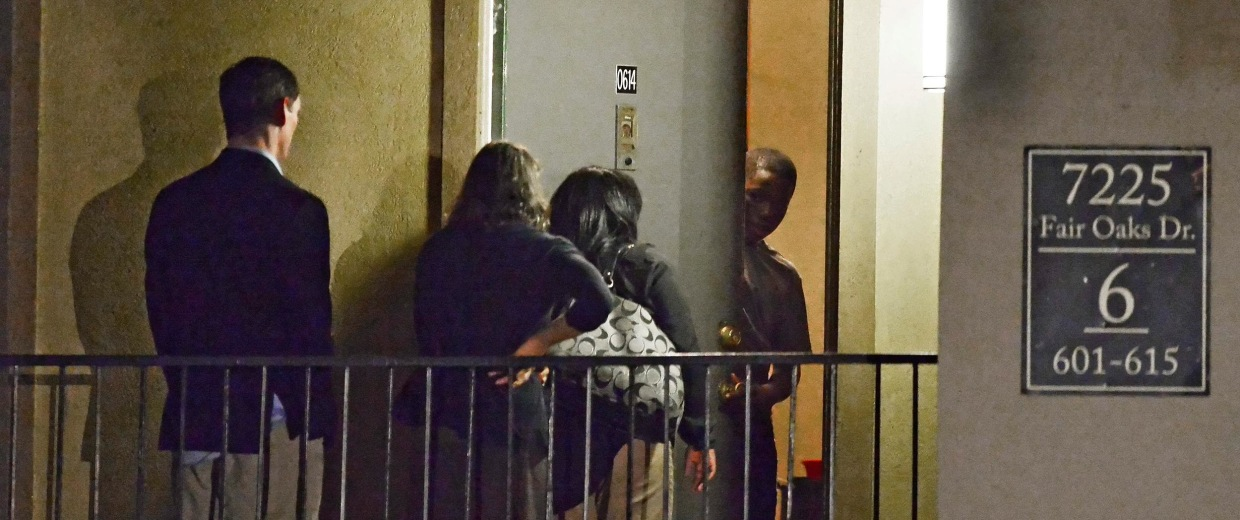 Image: An unidentified person opens the door for Dallas County Judge Clay Jenkins (L) along with two women at the apartment where Thomas Eric Duncan, an Ebola patient, was staying