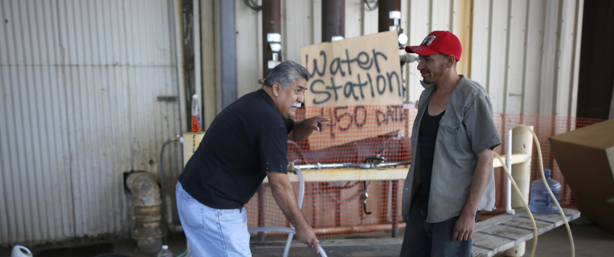 Image: Pastor Frankie Olmedo, who volunteers four hours a day to hand out water, fills up a container for Luis Bocanegra, 35, in Porterville, California