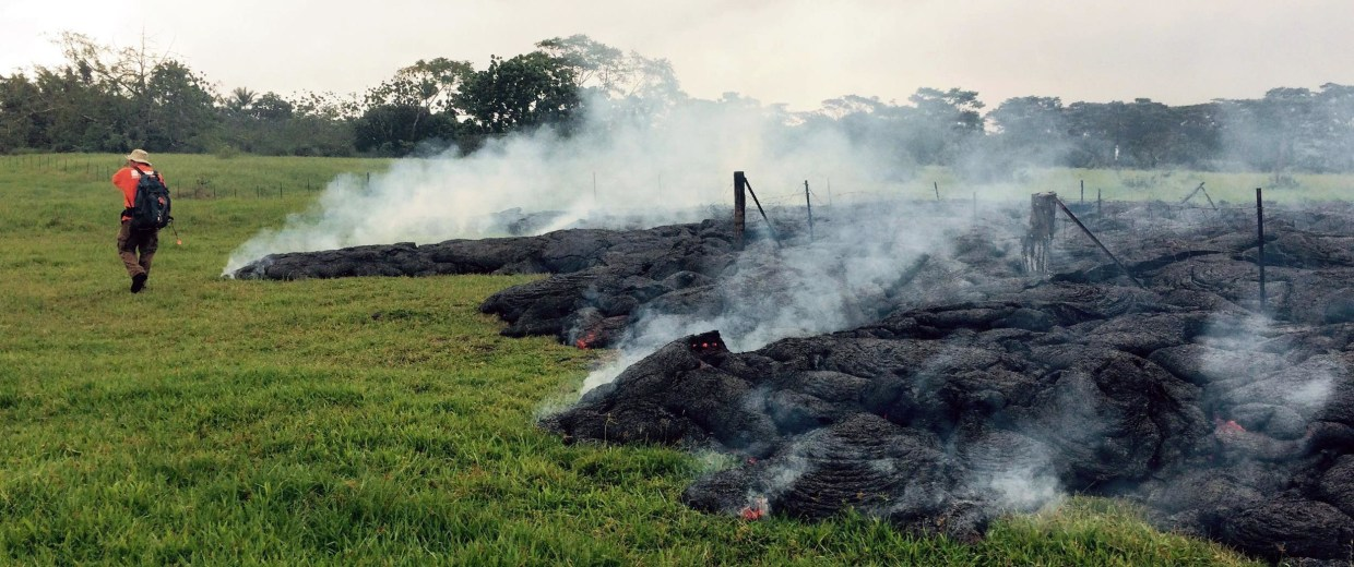 Image: A Hawaii Volcano Observatory geologist mapping the margin of the June 27 lava flow in the open field below Cemetery Road near the town of Pahoa on the Big Island of Hawaii, on Oct. 26.